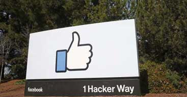 Facebook company entrance sign showing thumbs up logo